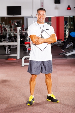 fitness trainer: handsome male gym trainer portrait inside gym
