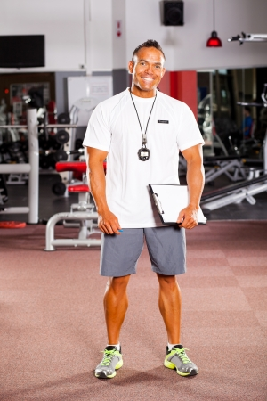 happy male trainer inside gym  photo