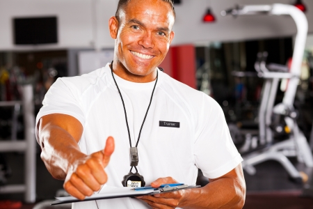 happy male gym trainer giving thumb up photo