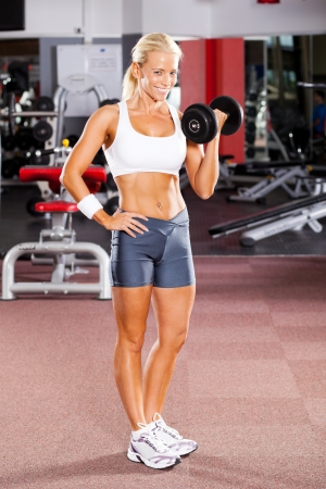 fitness woman using dumbbell in gym photo
