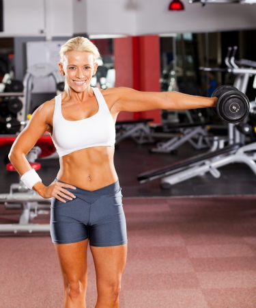 active young woman exercising with dumbbell photo