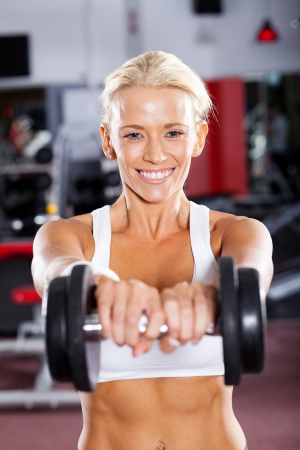 active young woman doing workout using dumbbell photo