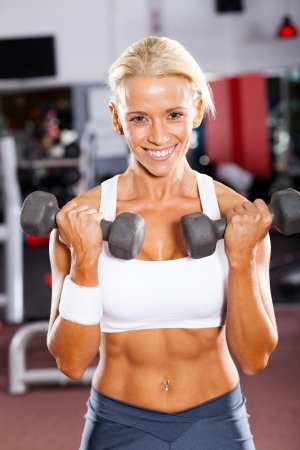 fitness woman exercising with dumbbells in gym photo