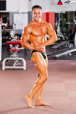 male bodybuilder posing in gym  photo