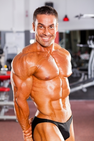 athletic body: happy male bodybuilder flexing muscle