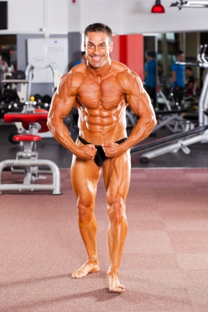 athletic body: male bodybuilder flexing his muscle in gym