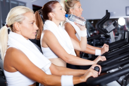 young woman drinking water while cycling in gym photo