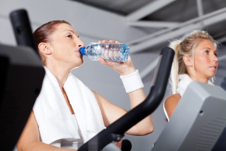 young woman drinking water while exercising in gym photo