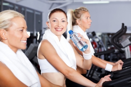young woman drinking water in gym photo