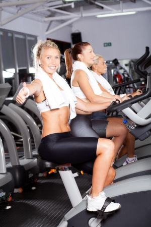 young woman giving thumb up on gym bike photo