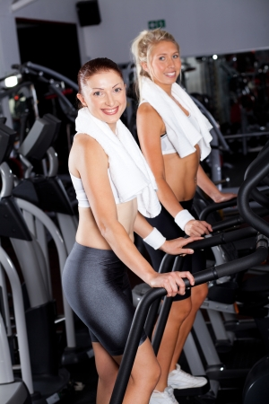 two young women exercising on gym stepper machine photo