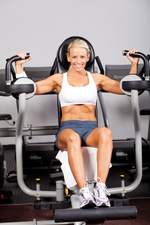 peck: fitness woman using peck deck machine in gym