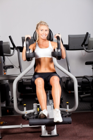 peck: young woman workout with peck deck machine in gym Stock Photo