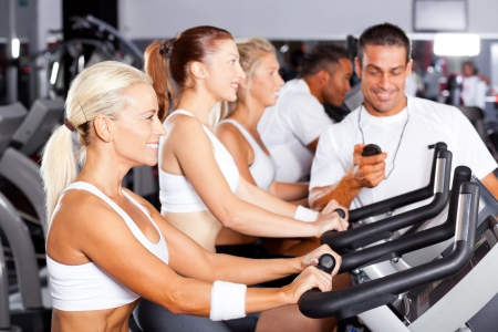 professional gym trainer monitoring trainees cycling performance photo