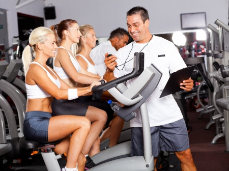 sport coach timing cyclist on gym bike photo