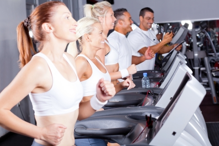 group of fitness people exercising with treadmill in gym photo