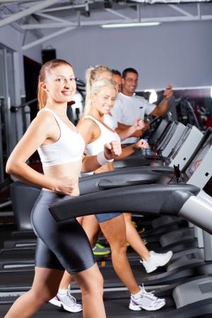 kardio: csoport fitness ember fut a futópadon, tornaterem