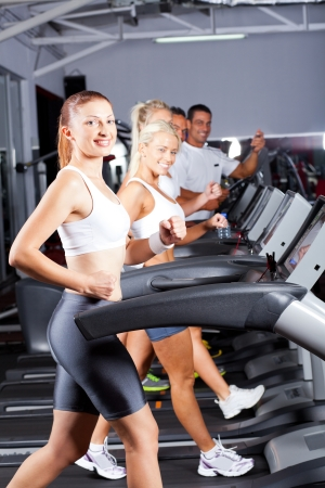 working out: group of fitness people running on treadmill in gym