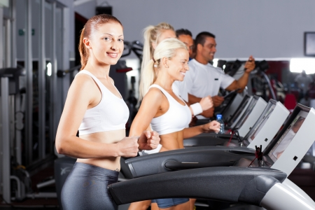 fitness people running on treadmill in gym photo