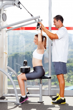 fitness woman in gym with personal trainer photo