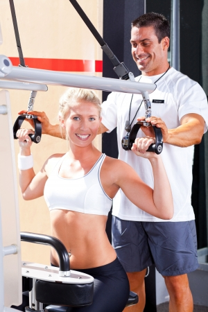 personal trainer: personal trainer helping client in gym