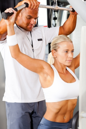 fitness woman and personal trainer in gym photo