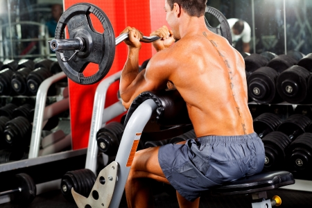 body building: man working out with barbell in gym