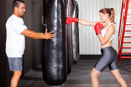woman boxing gloves: fitness woman training with punch bag in gym with personal trainer Stock Photo