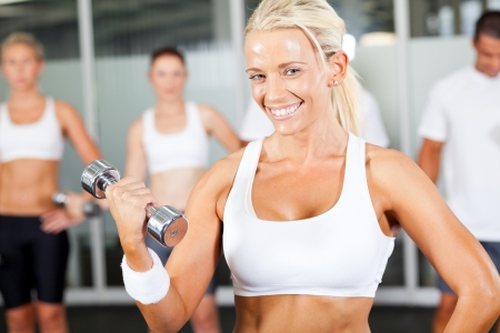 young fitness woman doing dumbbell exercise in gym  photo