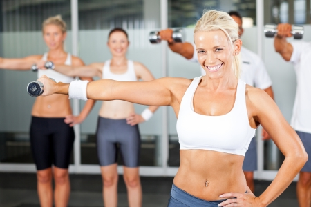 group of people exercise in gym with dumbbells photo
