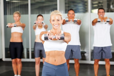 group of people doing aerobics with dumbbells in gym photo