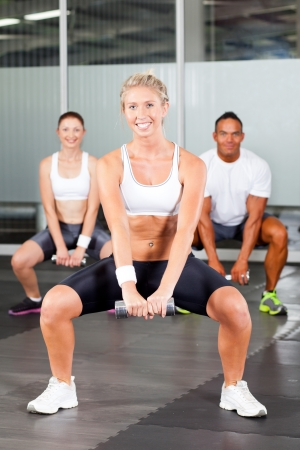 group of people doing fitness exercise with dumbbell in gym photo