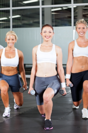 group of fitness woman using dumbbells in gym photo