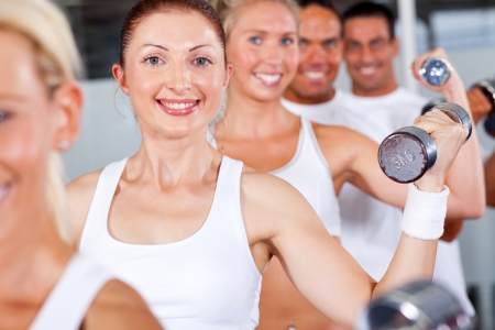 group of fitness people lifting weight in gym photo