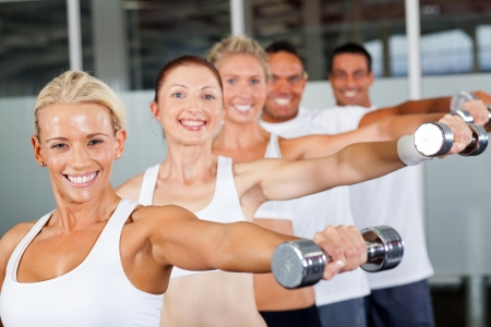aerobic training: group of people working out with dumbbells in gym