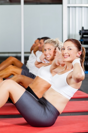 situp: group of people doing situps in gym