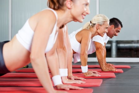 aerobic exercise: group of fitness people doing pushups in gym