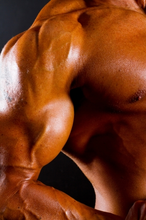 body building: closeup of athletic torso and arm on black background Stock Photo