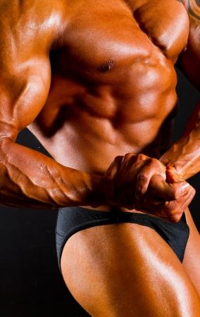 veiny: male bodybuilders body on black background