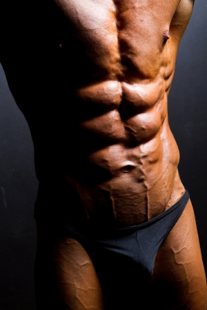veiny: closeup of bodybuilder abdomen on black background