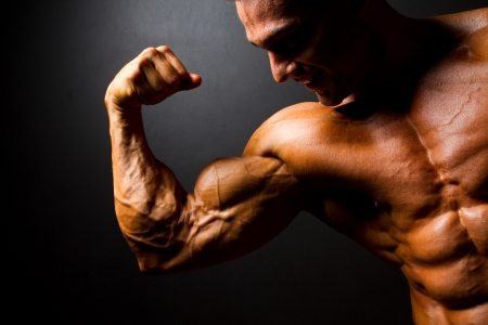 tanned body: strong bodybuilder posing on black background