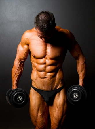 tanned body: bodybuilder with dumbbells on black background Stock Photo