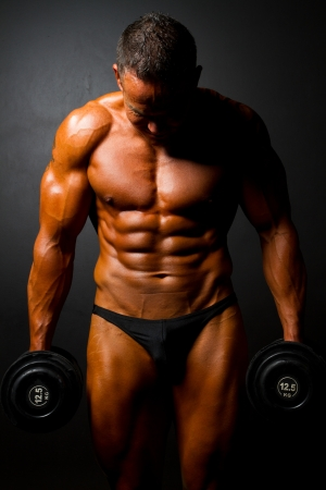 sixpacks: muscular man with dumbbells on black background Stock Photo