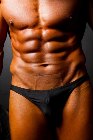body building: muscular mans body on black background