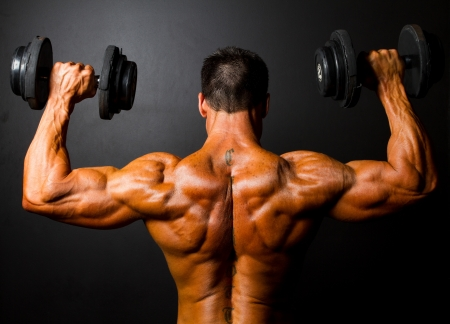 abdominal muscles: rear view of bodybuilder training with dumbbells on black background