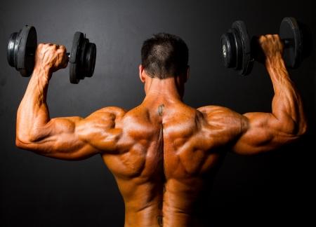 vista posteriore della formazione bodybuilder con manubri su sfondo nero Archivio Fotografico