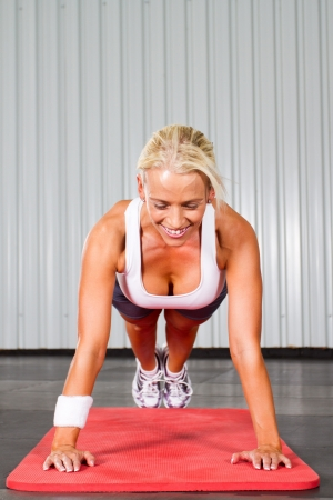 young fitness woman doing push ups  photo