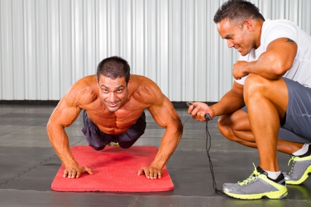 pushup: fitness man and personal trainer in gym doing push-ups