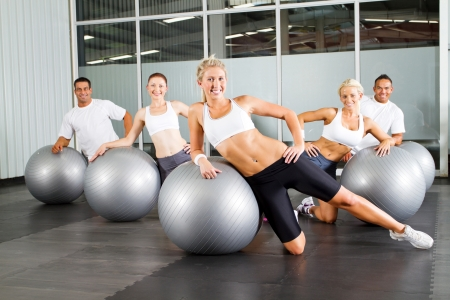 group of people doing workout with gymnastic ball in a gym