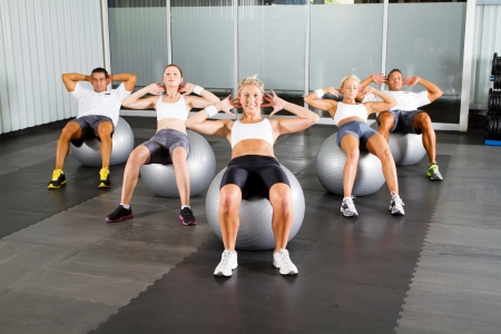 group of people doing workout with fitness balls in gym photo